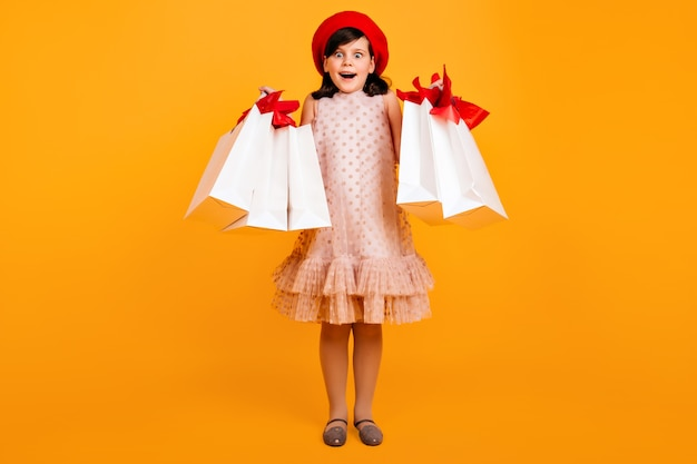 買い物の後にポーズをとっているフランスのベレー帽の驚いた少女。紙袋で驚いた子供。 無料写真