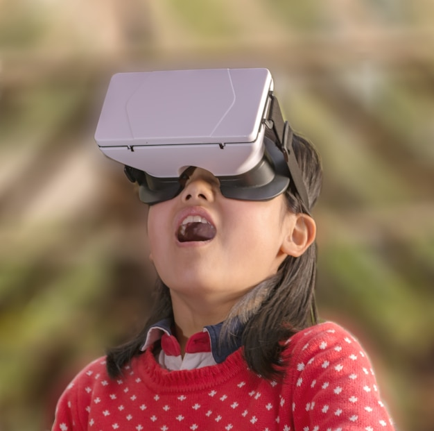 Surprised little girl with a virtual glasses Free Photo
