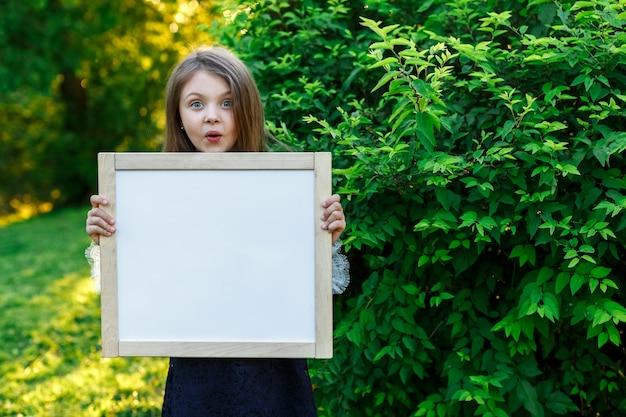 Удивленная маленькая школьница держит доску летом Premium Фотографии