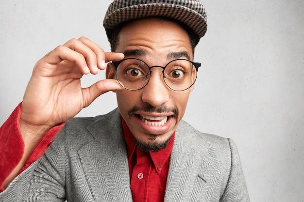 驚いた男性のオタクは、丸い眼鏡をかけ、フレームに手をつないで、キャップとジャケットを着用し、ぎこちなく見えます、 無料写真