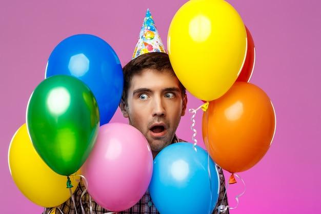 놀란 된 남자 생일을 축 하, 보라색 벽 위에 다채로운 Baloons를 들고. 무료 사진