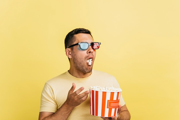 Surprised man eating popcorn with copy space Free Photo