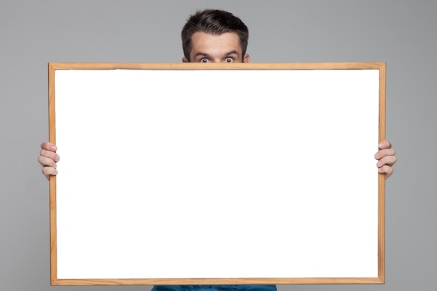 Surprised man showing empty white board Free Photo