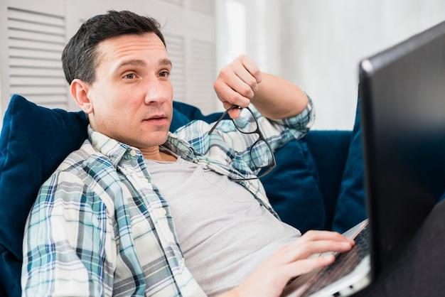 Surprised man using laptop on settee Free Photo