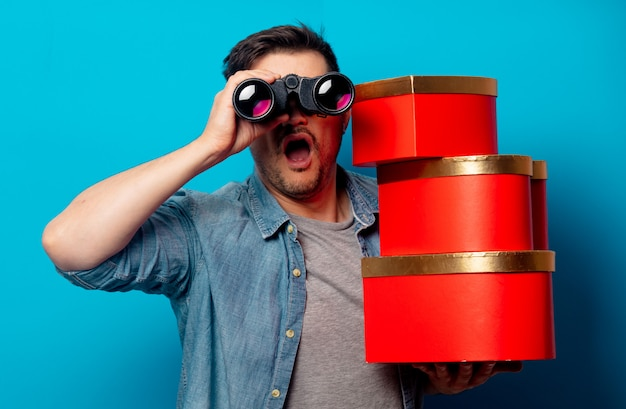 Surprised man with binoculars and red gifts Premium Photo