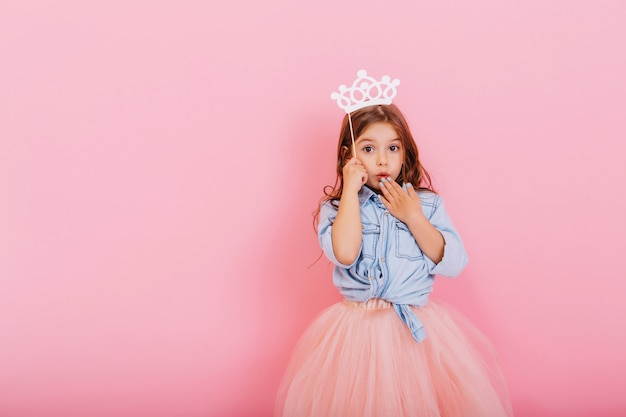 Surprised pretty young girl in tulle skirt with crown on head expressing isolated on pink background. amazing cute little princess at carnival. place for text Free Photo