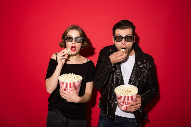Surprised punk couple eating popcorn and looking Free Photo