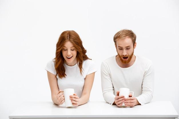 Удивленный рыжий мужчина, женщина смотрит кофейную гущу Бесплатные Фотографии