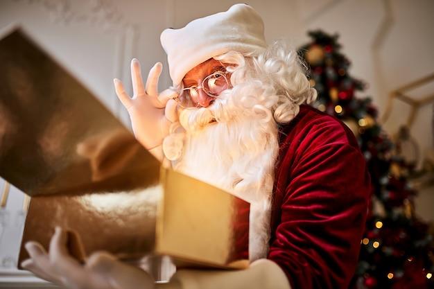 美しいクリスマスツリーの近くに魔法の光る贈り物を持って驚いたサンタクロース。 Premium写真