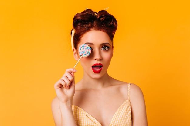 막대 사탕을 들고 놀된 관능적 인 여자입니다. 달콤한 사탕과 매력적인 핀 업 소녀의 스튜디오 샷. 무료 사진