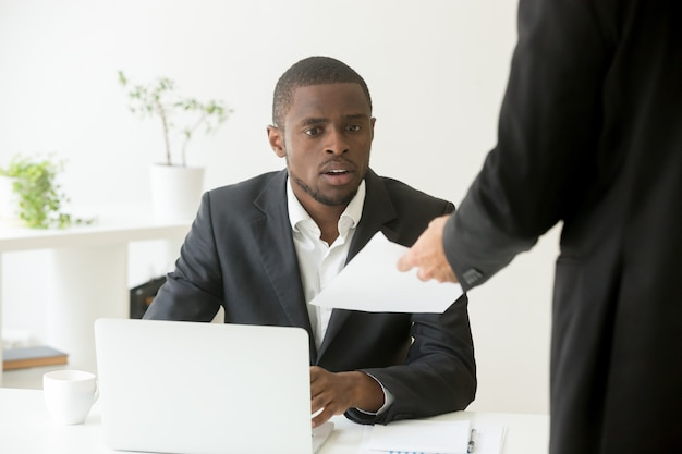 Surprised shocked african businessman getting unexpected notice from caucasian colleague Free Photo