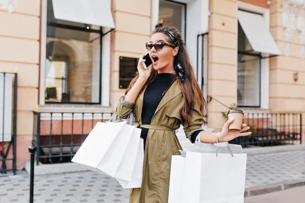 Удивленная женщина-шопоголик узнала о больших скидках в магазине во время разговора с другом Бесплатные Фотографии