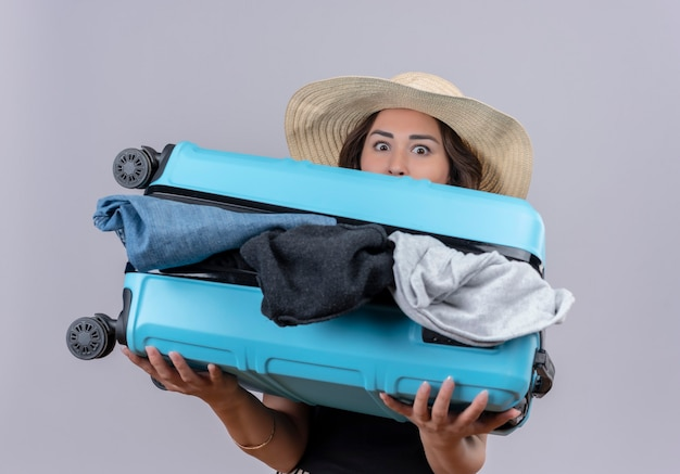 Surprised traveler young girl wearing black undershirt in hat holding open suitcase on white background Free Photo