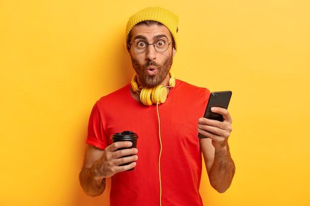 Ragazzo con la barba lunga sorpreso ascolta la musica in cuffia, invia messaggi di testo sul cellulare, digita la risposta Foto Gratuite
