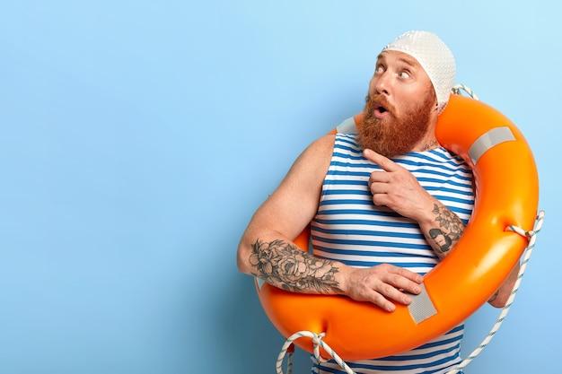 Bathingcap과 줄무늬 조끼를 입고 놀란 형태가 이루어지지 않은 남성 휴가객 무료 사진