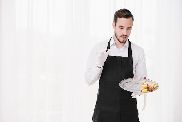 Surprised waiter holding plate Free Photo