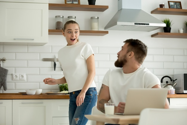 Surprised wife excited to hear news from husband in kitchen Free Photo