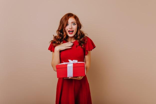 プレゼントを持っている赤いドレスで驚いた女性。誕生日を祝う魅力的な生姜の女の子。 無料写真