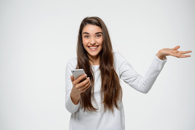 驚いた女性がスマートフォンで素晴らしいニュースを受け取る 無料写真