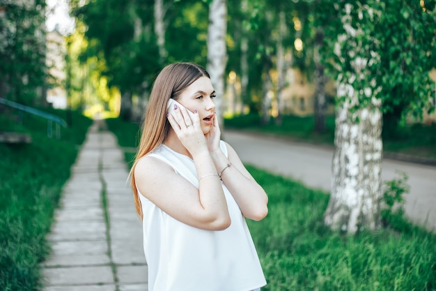 Surprised woman talking on mobile phone Premium Photo