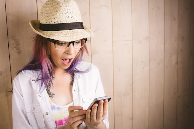 Surprised woman using mobile phone Premium Photo