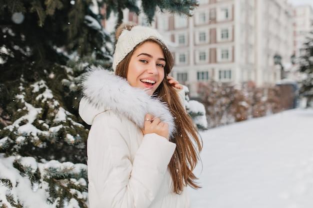 冬の休日で楽しんで、屋外の時間を費やして長いストレートの髪を持つ驚く女性。雪の日に公園で身も凍るよう白い衣装で熱狂的な白人女性の肖像画。 無料写真
