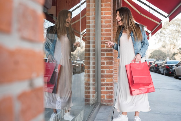 Surprised woman with shopping packets looking at shop windows Free Photo