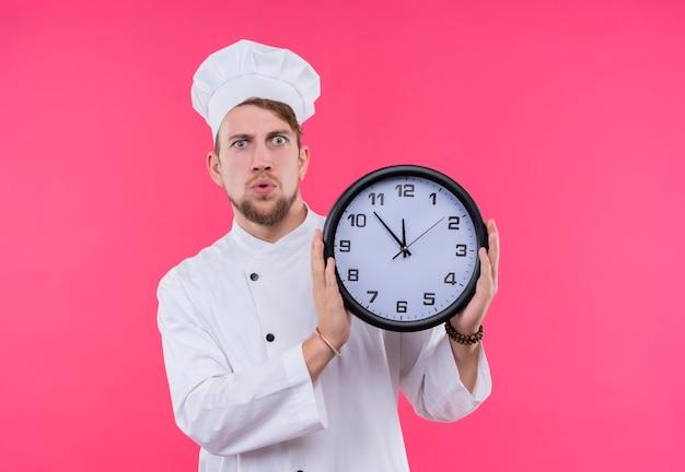 Un giovane chef barbuto sorpreso in uniforme bianca che mostra il tempo mentre si tiene l'orologio da parete su una parete rosa Foto Gratuite