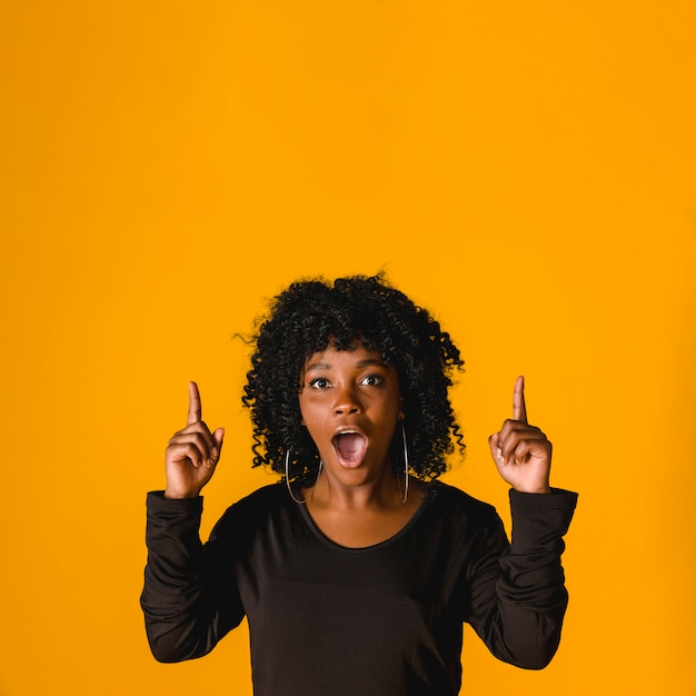 Surprised young black female pointing up in studio Free Photo