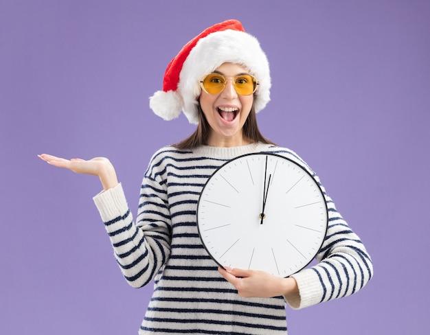Giovane ragazza caucasica sorpresa in occhiali da sole con l'orologio della tenuta del cappello della santa e che tiene la mano aperta Foto Gratuite
