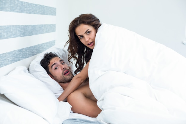 Surprised young couple enjoying on bed Premium Photo