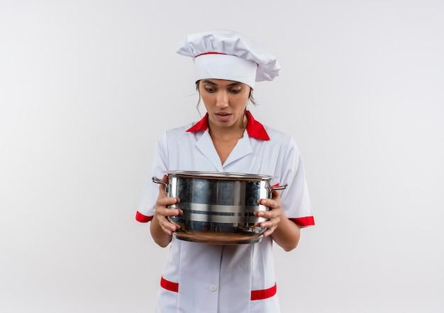 コピースペースのある鍋を持って見ているシェフの制服を着て驚いた若い女性料理人 無料写真