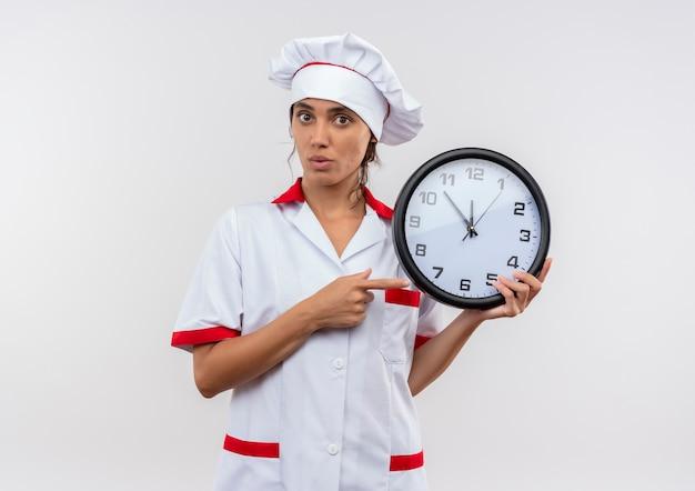 Giovane donna sorpresa che indossa la tenuta uniforme del cuoco unico e indica l'orologio da parete con lo spazio della copia Foto Gratuite