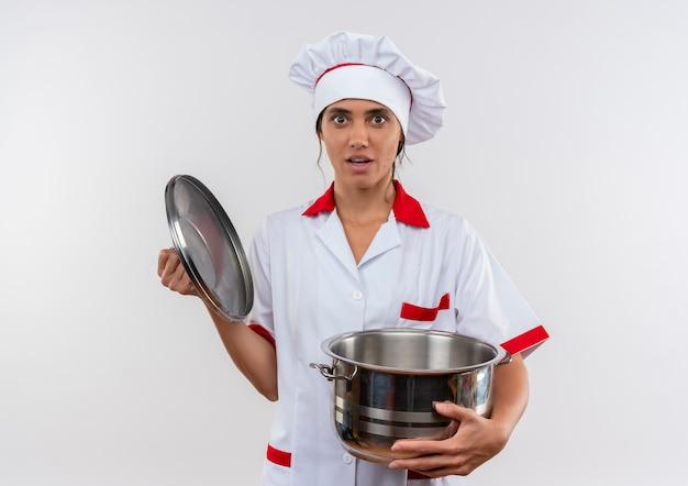 コピースペースと鍋と蓋を保持しているシェフの制服を着て驚いた若い女性料理人 無料写真