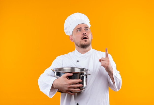 Surprised young handsome cook in chef uniform holding boiler and raising finger looking at right side on isolated orange space Free Photo