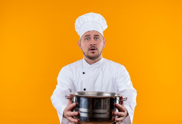 Surprised young handsome cook in chef uniform stretching out boiler  on isolated orange space Free Photo