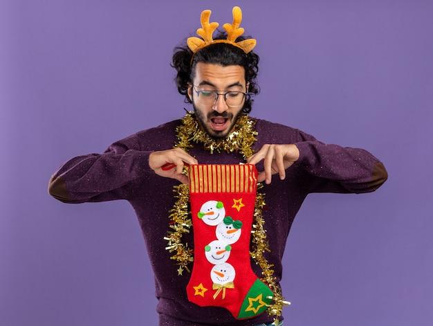 Удивленный молодой красивый парень в рождественском обруче для волос с гирляндой на шее держит и смотрит в рождественские носки, изолированные на синем фоне Бесплатные Фотографии
