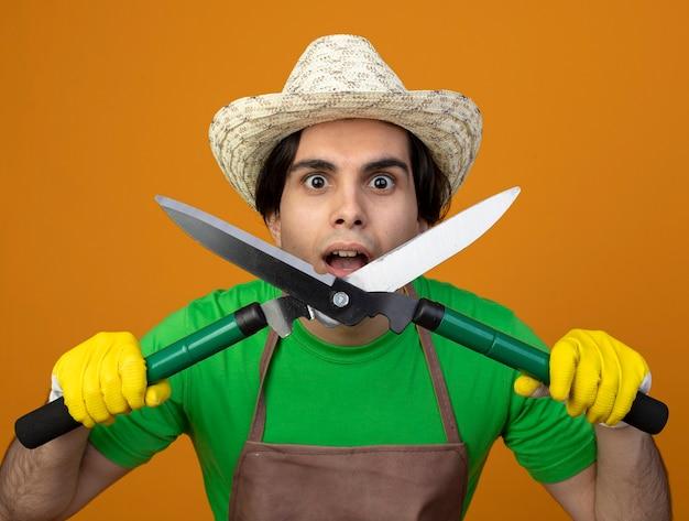 Giovane giardiniere maschio sorpreso in cappello da giardinaggio d'uso uniforme con i guanti che tengono i tagliatori isolati sulla parete arancione Foto Gratuite