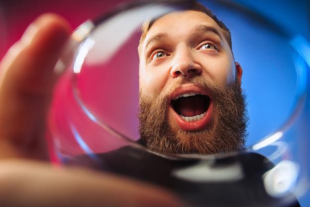 Удивленный молодой человек позирует с бокалом вина. эмоциональное мужское лицо Бесплатные Фотографии