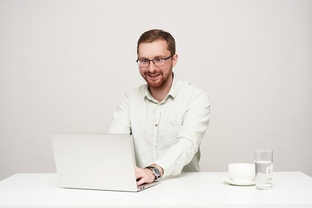 Giovane maschio biondo piuttosto barbuto sorpreso con gli occhiali guardando eccitato lo schermo del suo computer portatile durante la lettura di notizie inaspettate, in posa su sfondo bianco Foto Gratuite