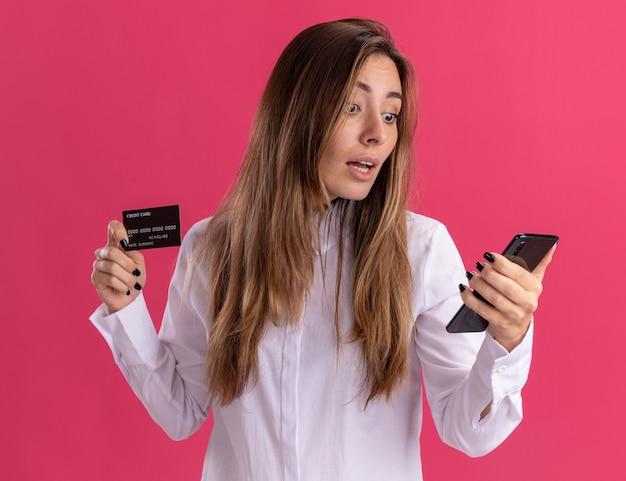 驚いた若いかなり白人の女の子はクレジットカードを保持し、コピースペースでピンクの壁に隔離された電話を見て 無料写真