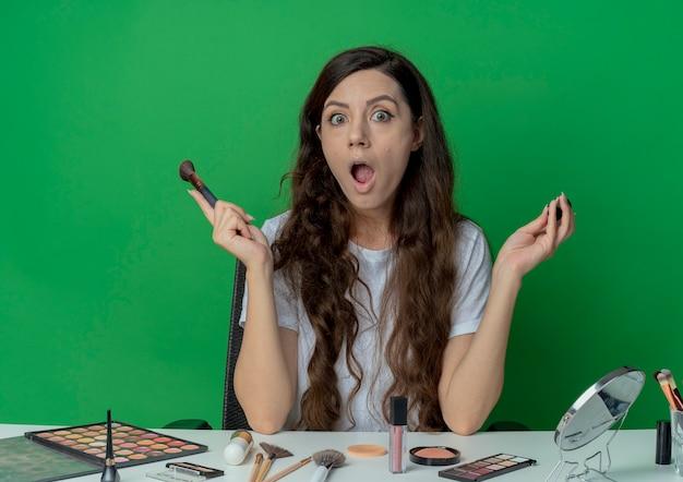 緑の背景に分離された赤面とパウダーブラシを保持している化粧ツールで化粧テーブルに座っている驚いた若いかわいい女の子 無料写真