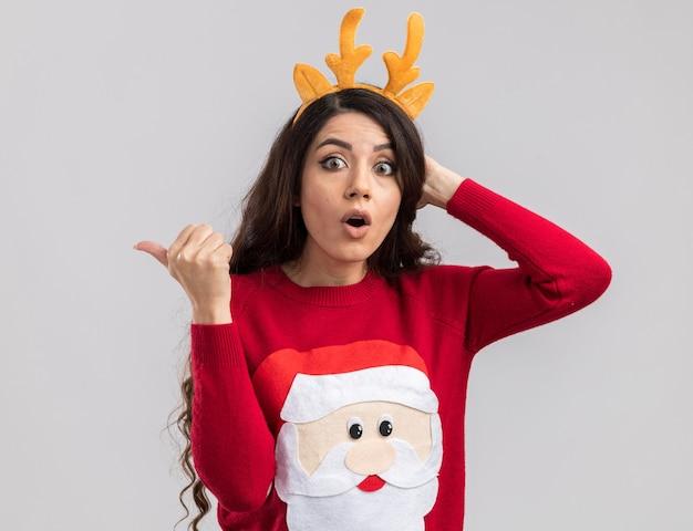 Giovane bella ragazza sorpresa che indossa la fascia dei corna delle renne e maglione del babbo natale che osserva mantenendo la mano sulla testa che indica a lato Foto Gratuite