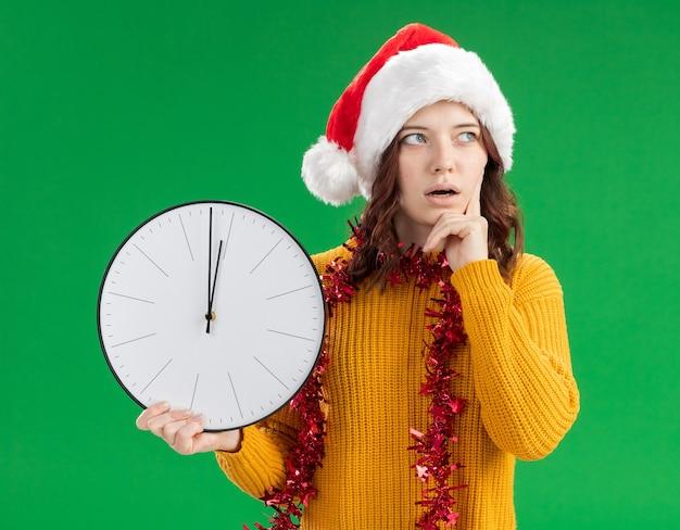 La giovane ragazza slava sorpresa con il cappello della santa e con la ghirlanda intorno al collo mette il dito sulla faccia e tiene l'orologio che guarda a lato Foto Gratuite