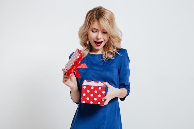 Удивленная молодая женщина, держащая подарочную коробку на белой стене Бесплатные Фотографии