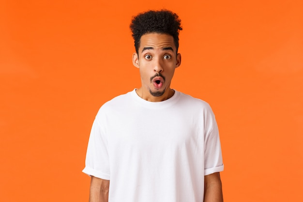 Surprises, amazement concept. astonished and impressed handsome young college student, african-american guy, folding lips staring amazed, gasping wondered say wow, standing orange Premium Photo