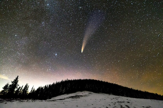 Surreal view of night in mountains with starry dark blue cloudy sky and c/2020 f3 (neowise) comet with light tail. Premium Photo