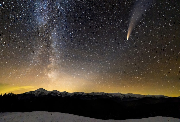 Surreal view of night in mountains with starry dark blue cloudy sky Premium Photo