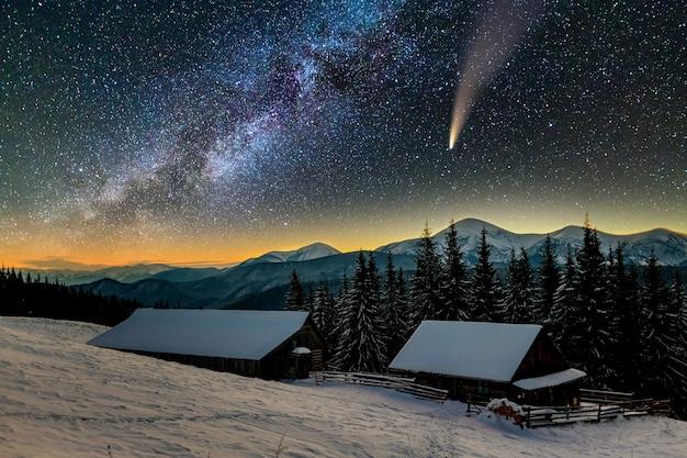 星空の濃い青の曇り空と明るい尾を持つc / 2020 f3(neowise)彗星の山の夜のシュールなビュー。 Premium写真