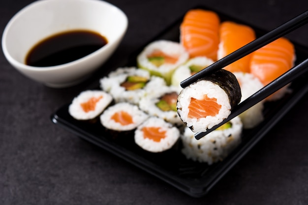 Sushi assortment on black tray and soy sauce. Premium Photo